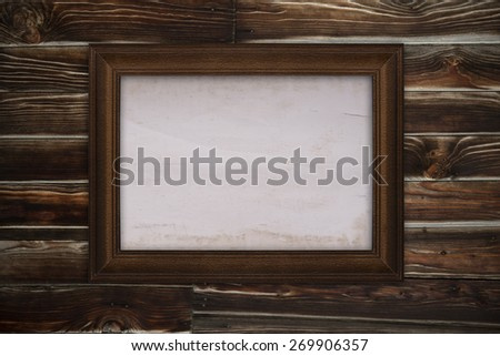 Wooden frame with old paper on wooden background - stock photo