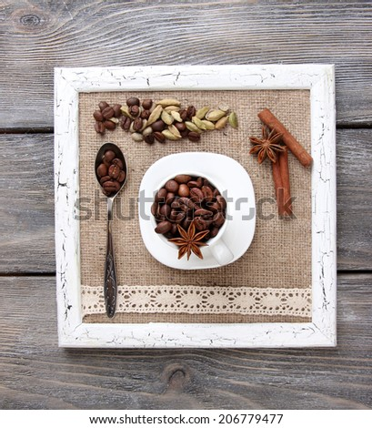 Wooden frame with white mug, coffee grains and spices on wooden background - stock photo