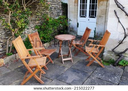 Wooden Garden Furniture on a Stone Patio - Garden Background - stock photo