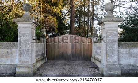 Wooden Gate and Surrounding Stone Wall of a Country Estate - stock photo