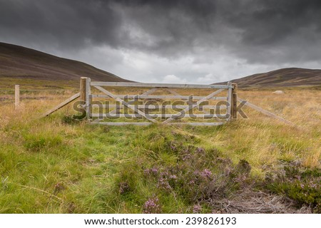 Wooden gate and wire fence on a meadow between hills in the Highlands of Scotland, UK - stock photo