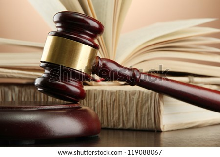 wooden gavel and books on wooden table,on brown background - stock photo