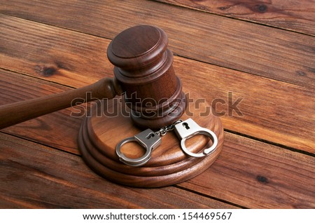 Wooden gavel and handcuffs on wooden background  - stock photo