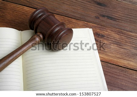 Wooden gavel and open book on wooden background - stock photo