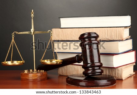 Wooden gavel, golden scales of justice  and books on grey background - stock photo