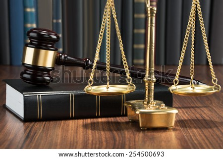 Wooden Gavel On Book With Golden Scale On Table - stock photo