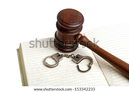 Wooden gavel, open notebook and handcuffs, isolated on white background - stock photo