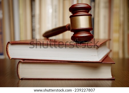 Wooden gavel resting on two large books conceptual of the judiciary, judgements, court and law enforcement - stock photo