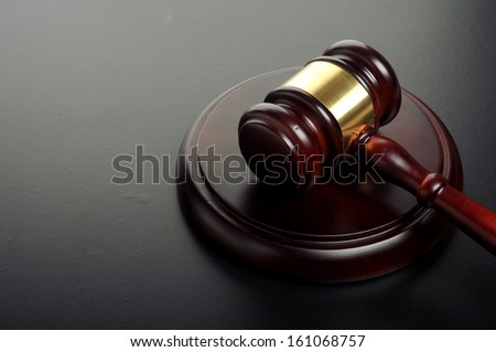 wooden gavel with golden ornament on a black background - stock photo