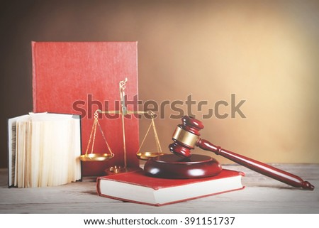 Wooden gavel with justice scales and books on brown background - stock photo