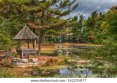 Wooden gazebo deep in the countryside forest and pond - stock photo