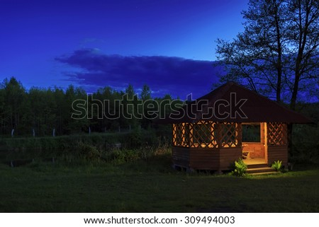 Wooden gazebo on the river bank at night