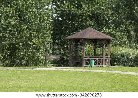 wooden gazebo with barbecue in a public park - stock photo