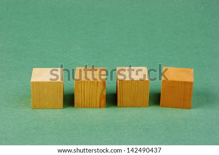 wooden geometric cube on a green background - stock photo