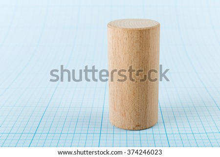 Wooden geometric shape cylinder on graph paper - stock photo