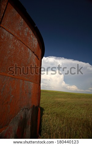 Wooden granary with Cumuloninumbus clouds in background - stock photo
