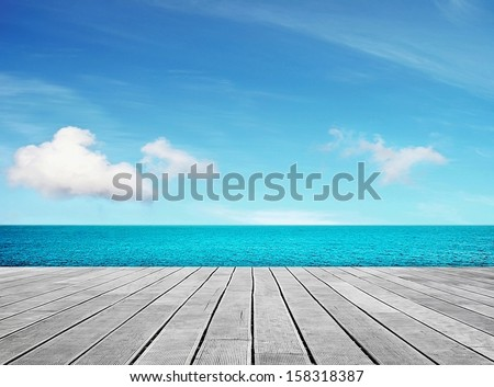 Wooden gray pier on sunny day with blue sky - stock photo