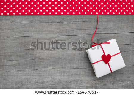 Wooden grey background with a present wrapped in paper with a red heart for christmas, valentine, mother's day or anniversary - for a greeting card - stock photo