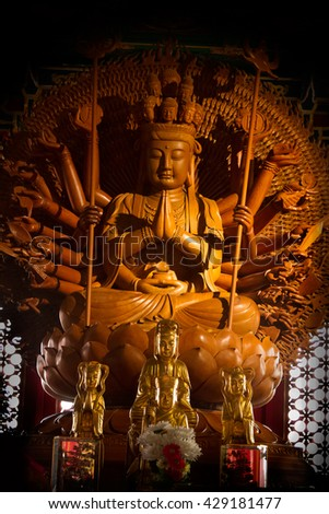 Wooden Guanyin buddha statue with thousand hands in Thailand - stock photo