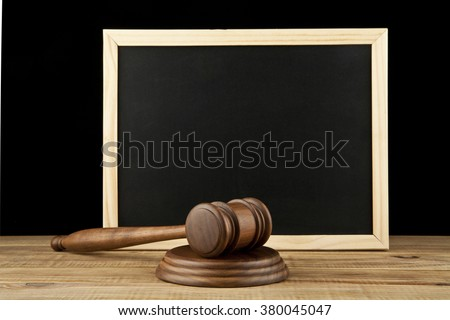 wooden hammer and a memo Board on black background - stock photo