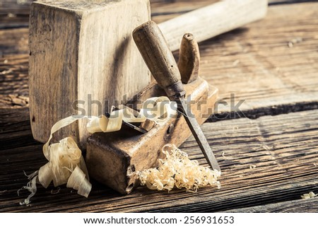 Wooden hammer, planer and chisel on wooden table - stock photo
