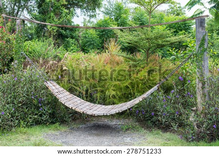 Wooden hammock in the peaceful garden. - stock photo
