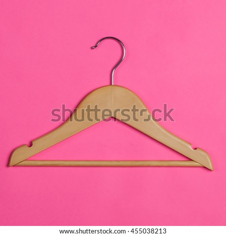 wooden hanger for hanging clothes on pink background - stock photo