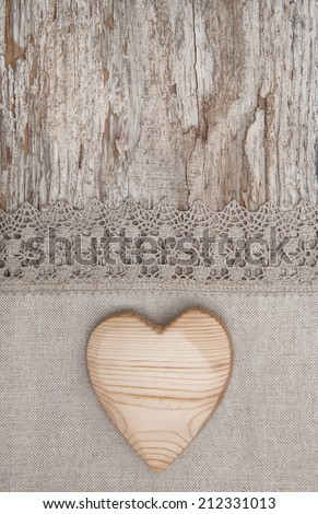 Wooden heart on the lace fabric and old wood - stock photo