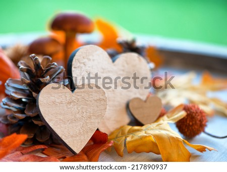 Wooden Hearts Amongst Autumn Foliage with Selective Focus - stock photo