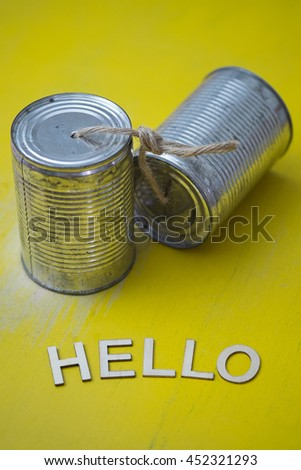 Wooden hello word on yellow grunge background with can phones - stock photo
