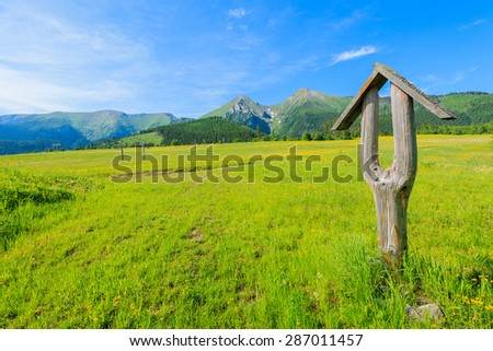 Wooden hiking trail sign on green meadow in summer landscape of Tatra Mountains, Slovakia - stock photo