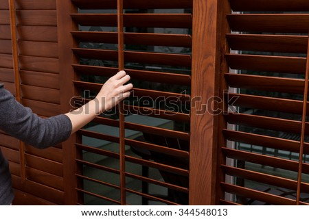 Wooden horizontal jalousie , Close , women hand - stock photo