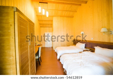 Wooden hotel room with two beds. - stock photo
