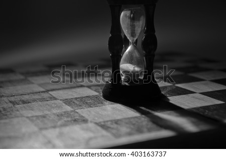 Wooden hourglass on an empty chess board (as the End of Game concept), in black and white, shallow DOF with selective focus - stock photo
