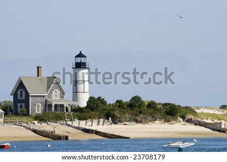 Wooden house and white lighthouse at Cape Cod near Portland - stock photo