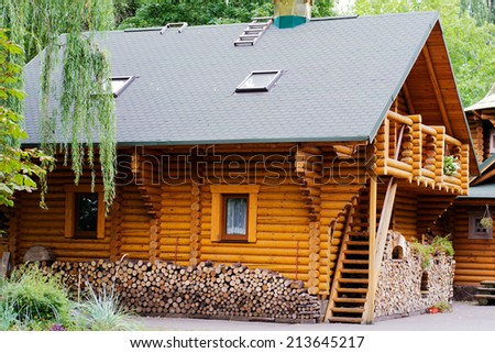 wooden house log house and a pile of chopped firewood - stock photo