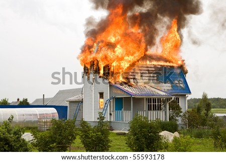 Wooden house on fire - stock photo