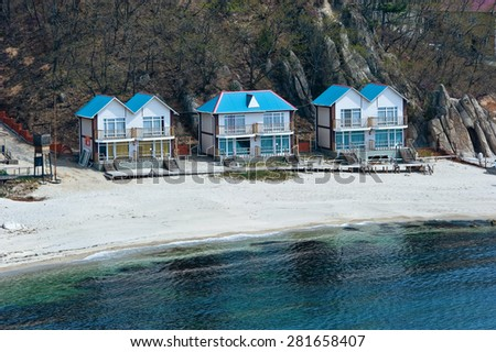 Wooden houses built on the coast. Far East of Russia. East (Japan) Sea. - stock photo