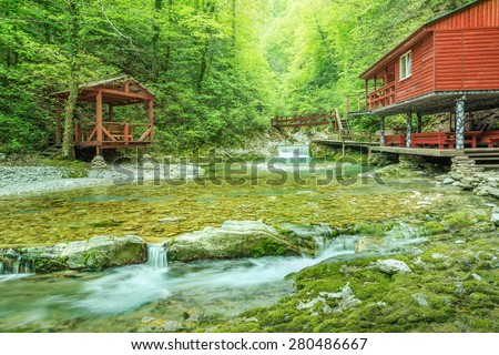 Wooden houses for the rest by the mountain river. - stock photo