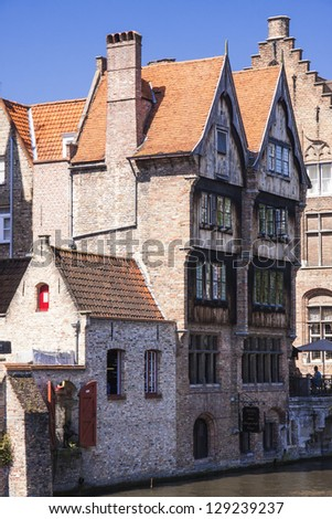 Wooden houses near canal in Bruges - stock photo