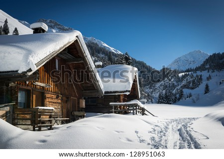 wooden houses on austrian mountains at winter with a lot of snow - stock photo