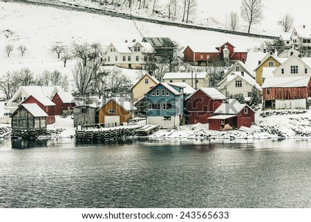 wooden houses on the banks of the Norwegian fjord, beautiful mountain landscape in winter - stock photo