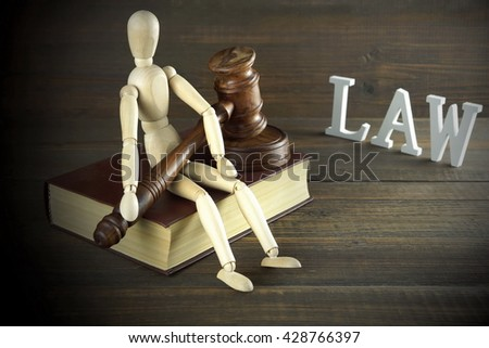 Wooden Human Figurine With  Judges Or  Auctioneer Gavel In Hand Sit On Red Book And White Sign Law On The Rough And Grunge Wooden Table, Close Up, Front View, Effects - stock photo