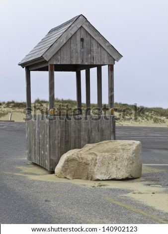 Wooden hut for attendant at entrance to vacant parking lot of beach on Cape Cod - stock photo