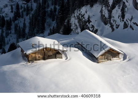Wooden huts in the snow. - stock photo