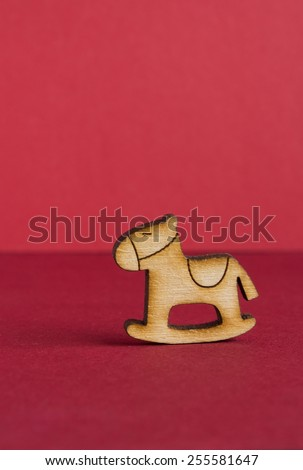 Wooden icon of children's rocking horse on red background vertical. - stock photo