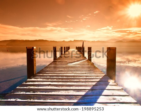 wooden jetty (68) at a little lake in upper bavaria with mountains in background - stock photo