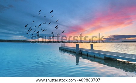 wooden jetty at lake, photographed in the evening, sunset in summer                          - stock photo