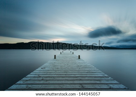 Wooden jetty at sunset, Lake Windermere in the English Lake District (UK) - stock photo