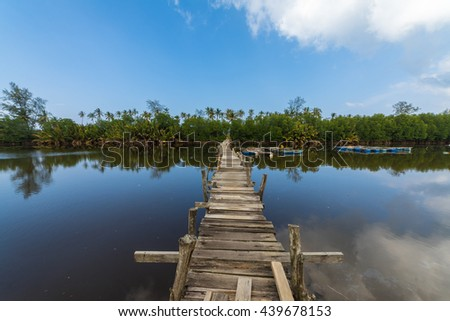 Wooden Jetty on a river in East Coast Malaysia and blue sky - stock photo